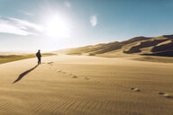 Hiker on sand at Great Sand Dunes National Park during sunny day - CAVF57939