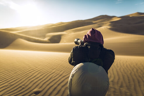 Rear view of hiker photographing with camera at Great Sand Dunes National Park - CAVF57942