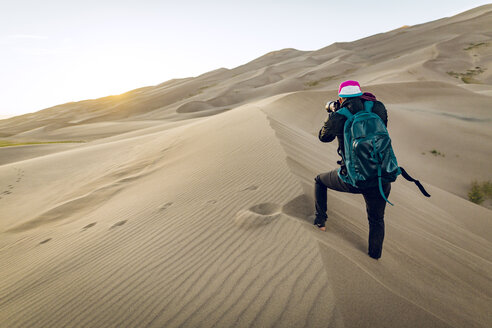 Rear view of hiker with backpack photographing at Great Sand Dunes National Park - CAVF57945
