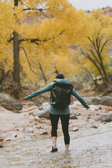 Rear view of hiker with backpack wading in stream during autumn at forest - CAVF57948