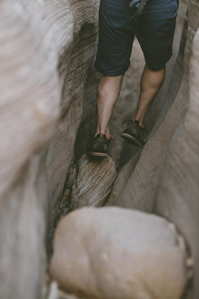 Low section of hiker canyoneering amidst narrow canyons - CAVF57951