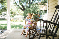 Girl having drink while sitting on rocking chair at porch - CAVF57963