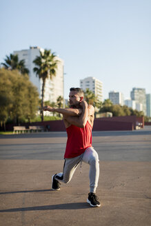 Fit man warming up before workout, doing lunges - MAUF01746