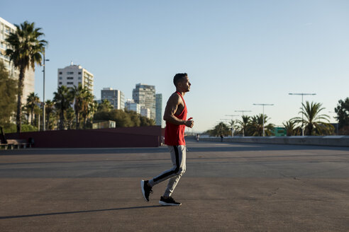 Muscular man jogging in the city - MAUF01755