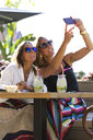 Happy girlfriends sitting outdoors with cocktail glasses taking a selfie - ERRF00235