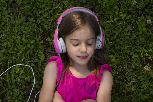 Portrait of girl lying on a meadow listening music with pink headphones - LVF07576