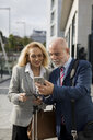Senior businessman and businesswoman with baggage using cell phones in the city - MAUF01776