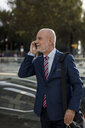 Senior businessman talking on cell phone in the city - MAUF01785