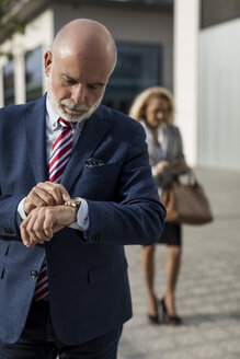 Senior businessman checking the time with businesswoman in background - MAUF01788