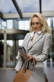Senior businesswoman using cell phone in foyer - MAUF01797