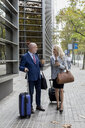 Senior businessman and businesswoman with baggage on the go in the city - MAUF01803