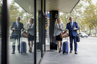 Senior businessman and businesswoman with baggage on the go in the city - MAUF01806
