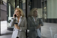 Senior businesswoman leaning against glass front talking on cell phone - MAUF01809