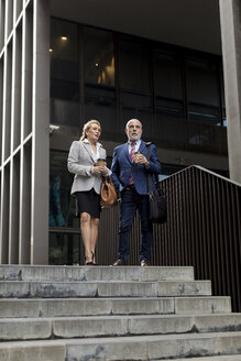 Senior businessman and businesswoman talking outside office building in the city - MAUF01812