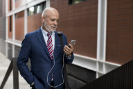 Senior businessman with cell phone and earphones outdoors - MAUF01815