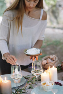 Woman preparing a romantic candlelight meal outdoors - ALBF00708