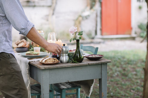 Close-up of man taking moka pot from garden table - ALBF00717