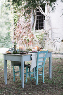 Laid garden table with candles next to a cottage - ALBF00720