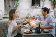 Happy couple having a romantic candelight meal next to a cottage - ALBF00729