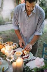 Man arranging a romantic candlelight meal outdoors - ALBF00735
