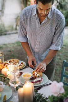 Man arranging a romantic candelight meal outdoors - ALBF00735