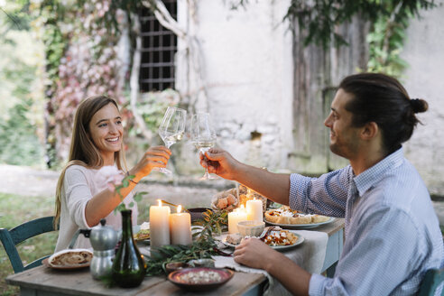 Couple having a romantic candlelight meal next to a cottage clinking wine glasses - ALBF00738