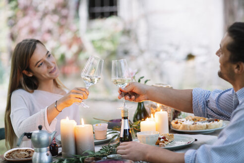 Couple having a romantic candlelight meal clinking wine glasses - ALBF00741