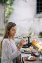 Woman tasting glass of wine at garden table - ALBF00744