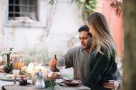 Romantic couple having a candlelight meal at garden table - ALBF00747