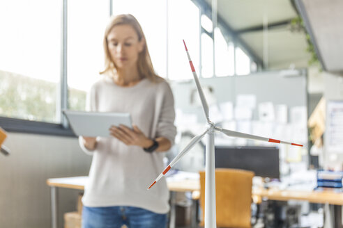 Woman in office with wind turbine model using tablet - TCF06015
