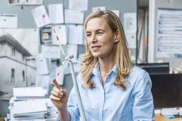 Confident woman in office holding wind turbine model - TCF06042