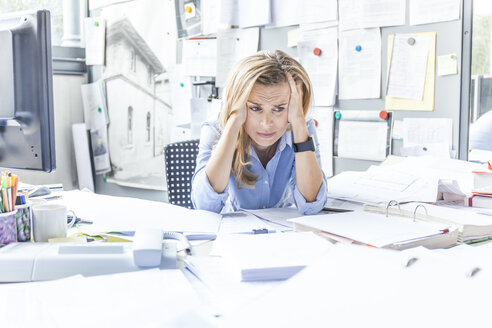 Despaired woman sitting at desk in office surrounded by paperwork - TCF06045