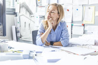 Pensive woman sitting at desk in office surrounded by paperwork - TCF06051