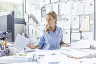 Woman sitting at desk in office doing paperwork - TCF06054