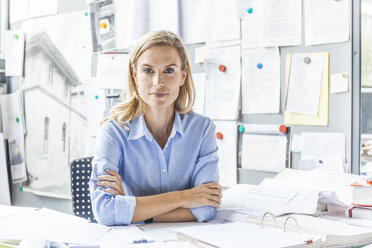 Portrait of confident woman sitting at desk in office surrounded by paperwork - TCF06057