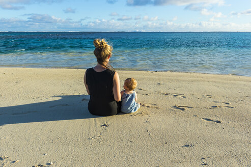Cook islands, Rarotonga, Woman sitting with her baby on a white sand beach - RUNF00306