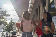 USA, Florida, Miami Beach, two happy female friends having a soft drink in the city - BOYF01162