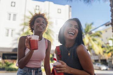 USA, Florida, Miami Beach, two happy female friends having a soft drink in the city - BOYF01171