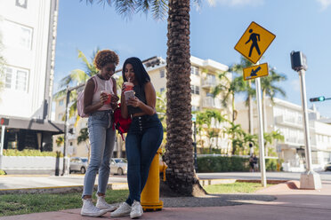 USA, Florida, Miami Beach, two happy female friends with cell phone and soft drink in the city - BOYF01174