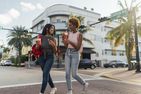 USA, Florida, Miami Beach, two happy female friends having a soft drink crossing the street - BOYF01177