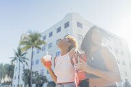 USA, Florida, Miami Beach, two happy female friends having a soft drink in the city - BOYF01186