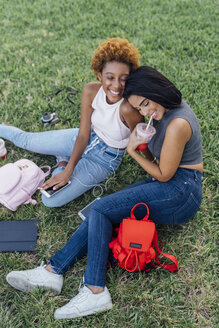 Two happy female friends relaxing in a park - BOYF01189