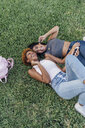Two happy female friends relaxing in a park listening to music - BOYF01192