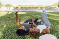 Two happy female friends relaxing in a park listening to music - BOYF01195