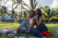 Two happy female friends relaxing in a park listening to music - BOYF01204