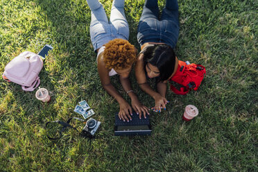 Two female friends relaxing in a park using a tablet - BOYF01207