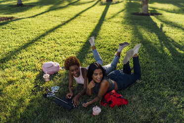 Two happy female friends relaxing in a park using a tablet - BOYF01213