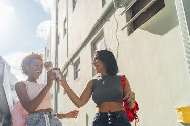 USA, Florida, Miami Beach, two happy female friends with ice cream cones in the city - BOYF01219