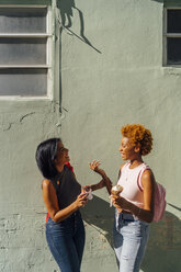 Two happy female friends with ice cream cones talking at a house wall - BOYF01222