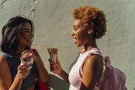Two happy female friends with ice cream cones talking at a wall - BOYF01225